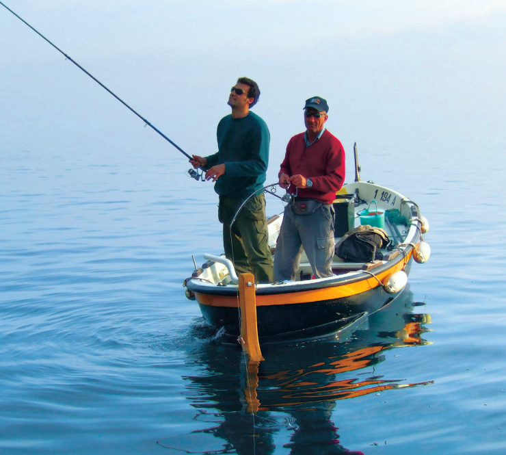 Momenti di pesca a bolentino su un tipico gozzo ligure in una bellissima giornata di mare calmo.
